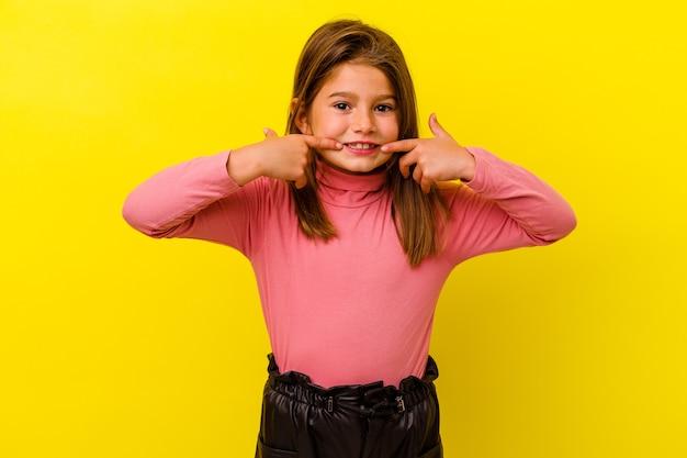 Klein kaukasisch meisje geïsoleerd op gele muur glimlacht, wijzende vingers naar mond.