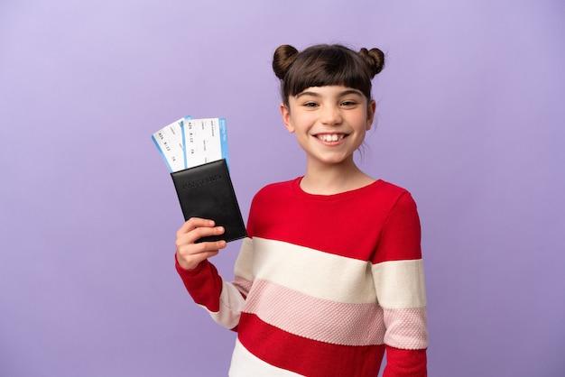 Klein kaukasisch meisje geïsoleerd op paars gelukkig in vakantie met paspoort en vliegtickets
