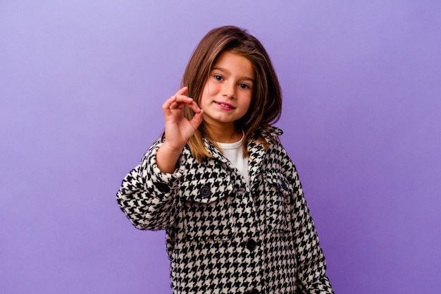 Klein kaukasisch meisje geïsoleerd op paarse muur vrolijk en zelfverzekerd tonend ok gebaar.