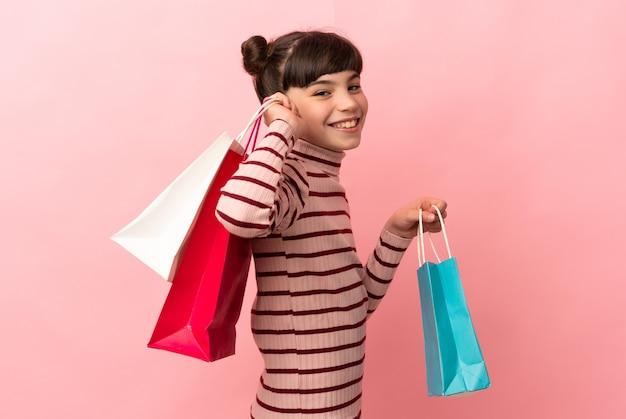 Klein kaukasisch meisje geïsoleerd op roze achtergrond met boodschappentassen en glimlachen
