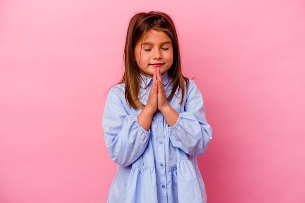 Klein kaukasisch meisje geïsoleerd op roze hand in hand bidden in de buurt van de mond, voelt zich zelfverzekerd.