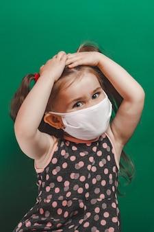 Klein kaukasisch meisje in medisch masker draagt rode polka dot jurk in studio op groene achtergrond en houdt haar hoofd pijn 2021