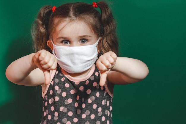 Klein kaukasisch meisje in medisch masker en polka dot jurk met duimteken op groene achtergrond tijdens quarantaine en coronavirus pandemie 2020
