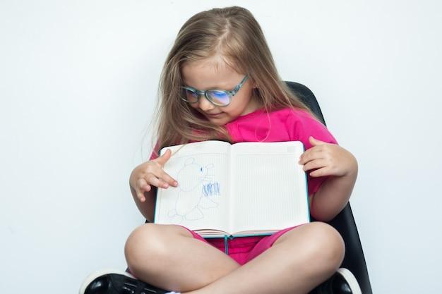 Klein kaukasisch meisje met blond haar en glazen, zittend in een stoel op een witte studiomuur