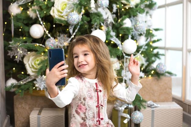 Klein kaukasisch meisje van de kerstboom maakt foto's van zichzelf met smartphone