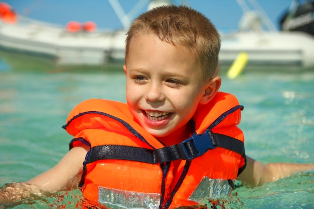 Klein kind aan de kust van het strand zwemmen op zee