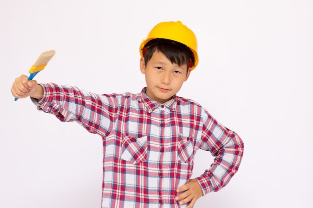 Klein kind als bouwvakker met een gele helm met een penseel in zijn hand