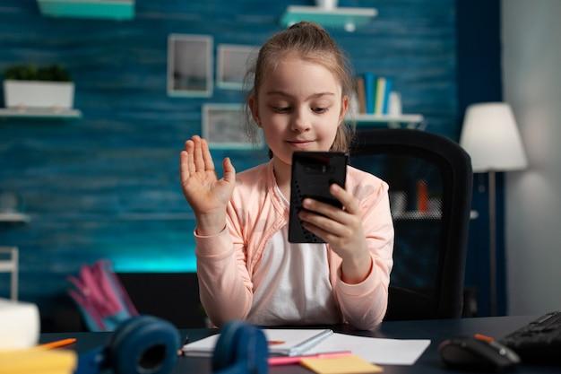 Klein kind begroet externe vriend tijdens online videocall-vergaderingsconferentie