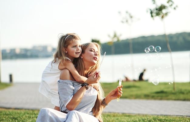 Klein kind blijft zich afvragen. foto van jonge moeder en haar dochter die goede tijd hebben op het groene gras met meer bij achtergrond.