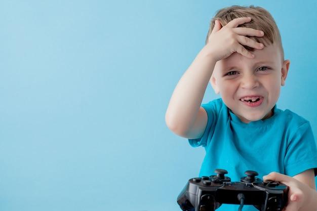 Klein kind dat blauwe kleren draagt, houdt joystick in de hand voor games op het blauwe portret van de kinderstudio