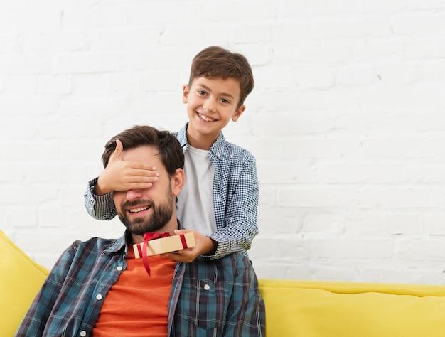 Klein kind een geschenk aanbieden aan zijn vader