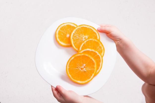 Klein kind houdt een witte plaat met plakjes sinaasappel op een witte achtergrond