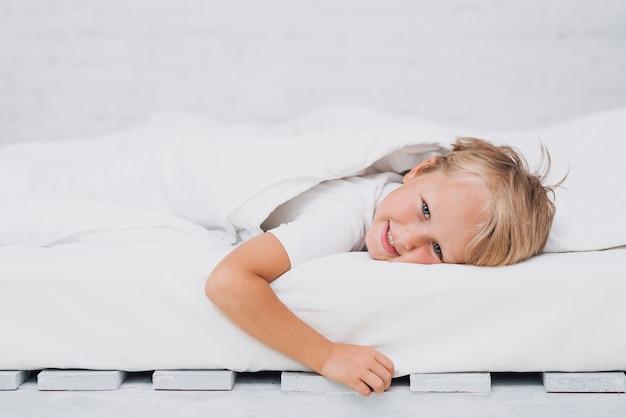 Klein kind in bed blijven tijdens het kijken naar de camera