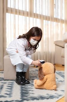 Klein kind in doktersuniform en medisch masker dat de temperatuur van een teddybeer neemt met een infraroodthermometer