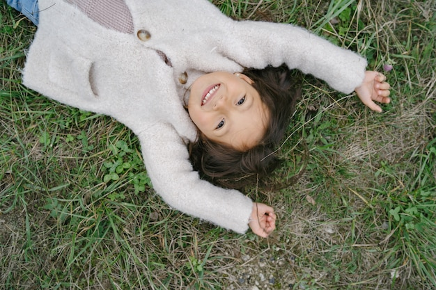 Klein kind in een schattige witte trui. meisje brengt tijd door in een park