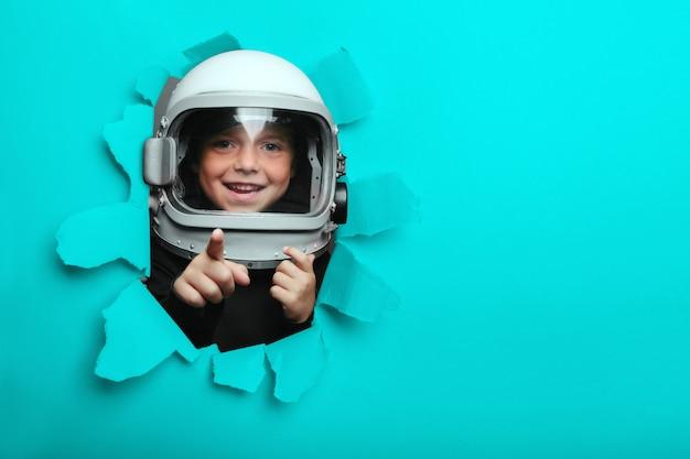 Klein kind in het dragen van een vliegtuighelm die door een gat van gekleurd document kijkt