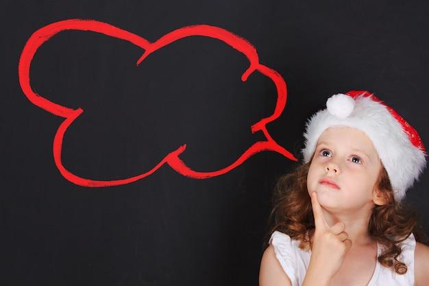 Klein kind in kerstmuts met dromen couds.