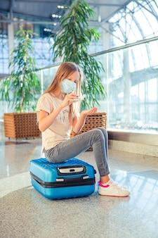 Klein kind in medisch masker in luchthaven wachten op instappen