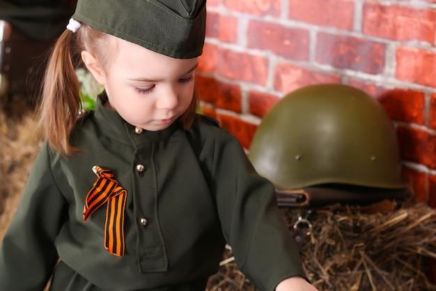 Klein kind in militair uniform op de feestdag van de overwinning; oorlogsversieringen. landelijke stijl.