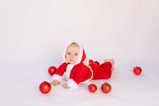 Klein kind in santa kostuum liggend op wit geïsoleerd, nieuwjaar en kerstmis concept