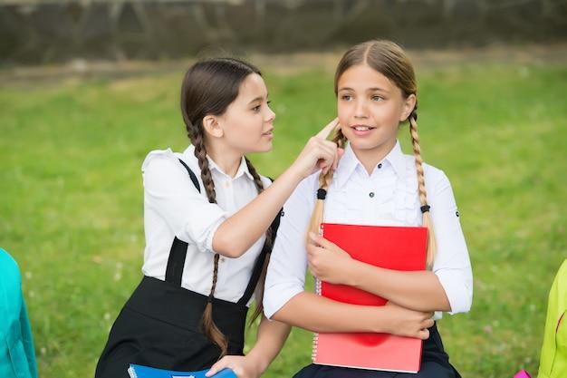 Klein kind in schooluniform touch huid van meisje klasgenoot zittend op een bankje, huidverzorging.