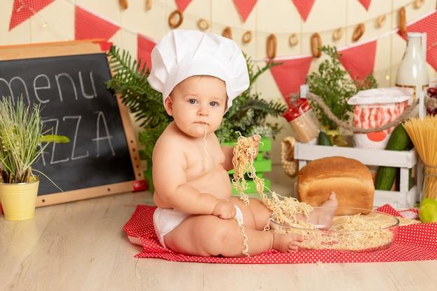 Klein kind kookt in een hoed in de keuken tussen de producten en eet spaghetti met zijn handen