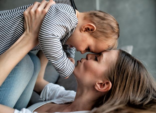 Klein kind lacht en blij met moeder op de bank