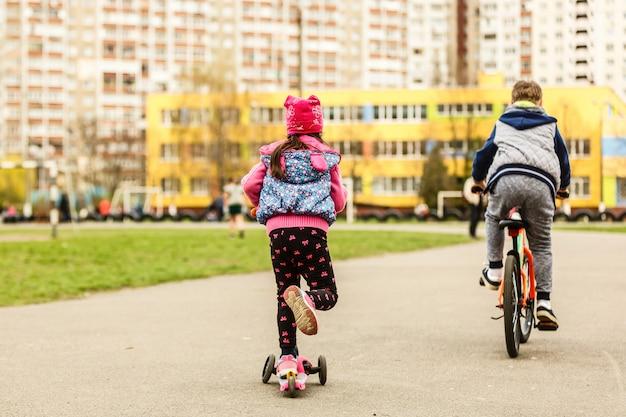 Klein kind leren rijden op een scooter in een stadspark op zonnige zomeravond. leuk meisje dat een rol berijdt. actieve vrije tijd en buitensport voor kinderen.