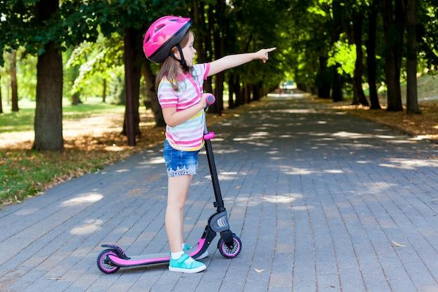 Klein kind leren rijden op een scooter in een stadspark op zonnige zomeravond.