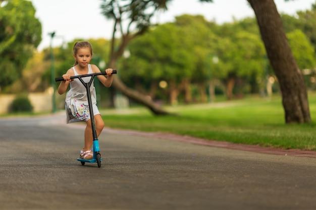 Klein kind leren rijden op een scooter in een stadspark op zonnige zomerdag