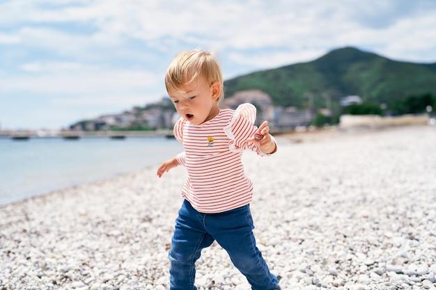Klein kind loopt langs een kiezelstrand met zijn mond open en kijkend naar zijn voeten
