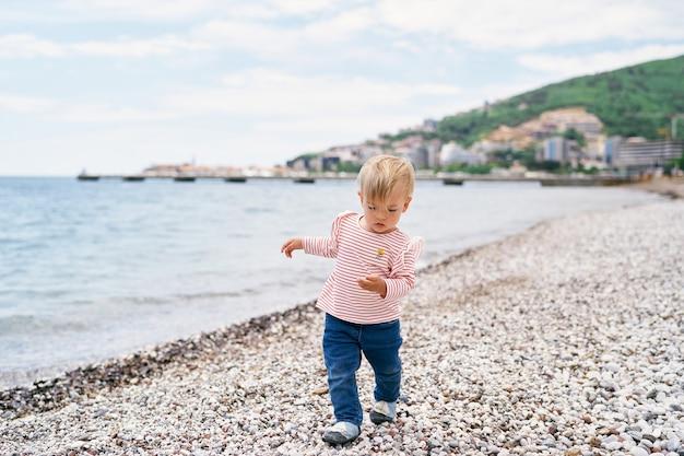 Klein kind loopt langs een strand in de buurt van de zee
