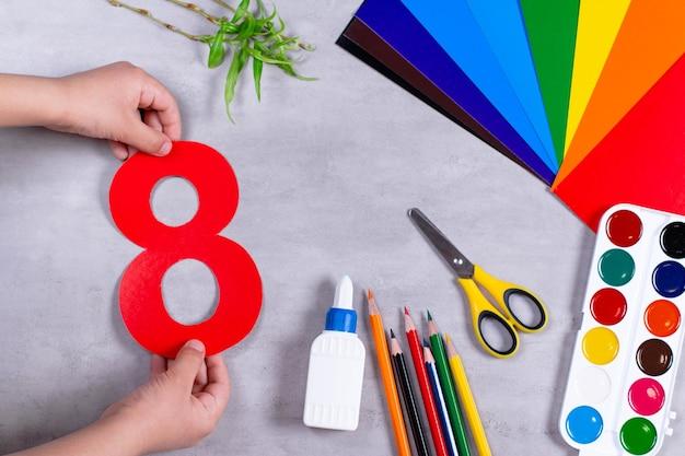 Klein kind maakt papierambachten voor moederdag. schaar, lijm, potlood op een tafel