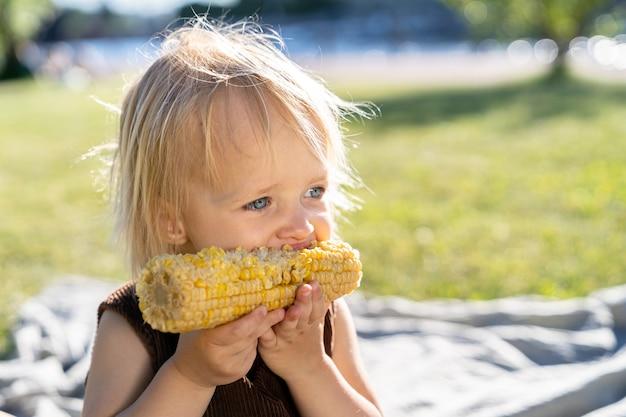 Klein kind meisje eet zoete maïskolf, zittend op plaid op gras in zomerdag. gezond eten.