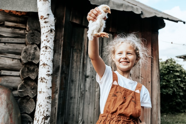 Klein kind meisje houdt de kip op de boerderij. portret van meisje met kip