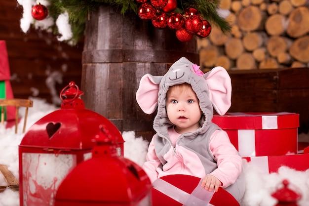 Klein kind (meisje) in feestelijke pak van muis (rat) zit in witte sneeuw in de buurt van geschenken en kerstversiering