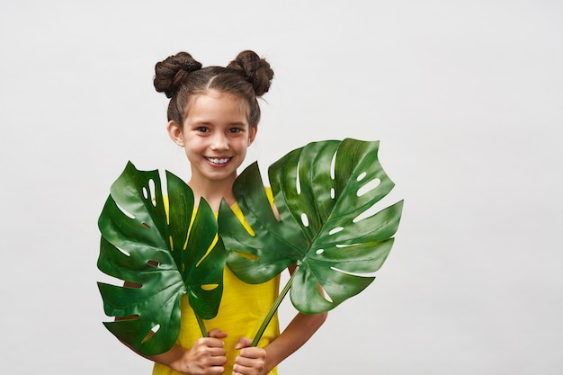 Klein kind meisje in gele jurk met grote bladeren monstera in handen