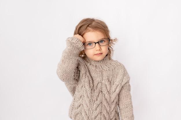 Klein kind meisje met bril op witte achtergrond, ruimte voor tekst