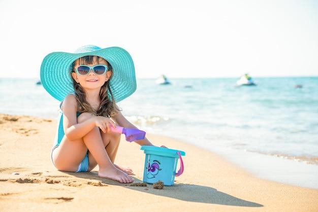 Klein kind meisje met hoed en zonnebril zit op het zand met een emmer
