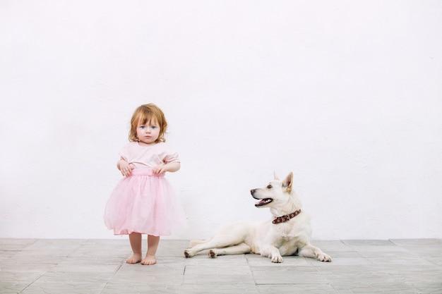Klein kind meisje mooi, schattig en blij met hond op witte muur achtergrond