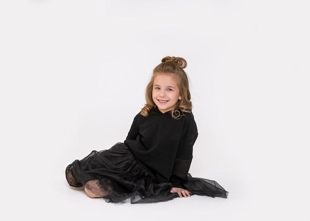 Klein kind meisje zittend op de vloer in de studio en camera kijken op witte achtergrond met glimlach. foto van volledige lengte