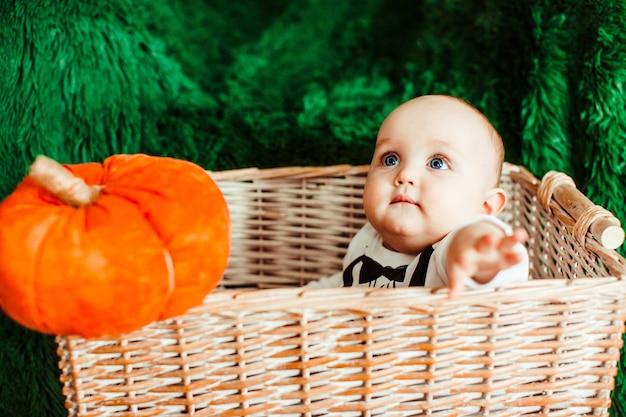 Klein kind met blauwe ogen zit in een mand met speelgoed pompoenen