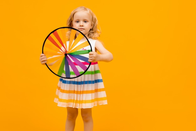 Klein kind met blond haar houdt een ronde speelgoed propeller op geel