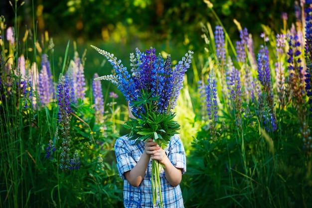 Klein kind met een boeket violette lupinebloemen die zijn gezicht op de achtergrond van planten verbergen hiding