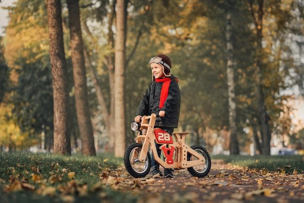 Klein kind met een loopfiets in bovenkleding in de herfst