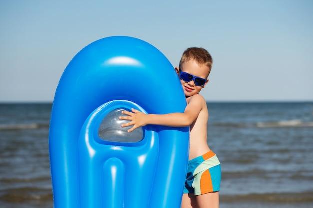 Klein kind met een opblaasbare matras op het strand op een warme zomerdag