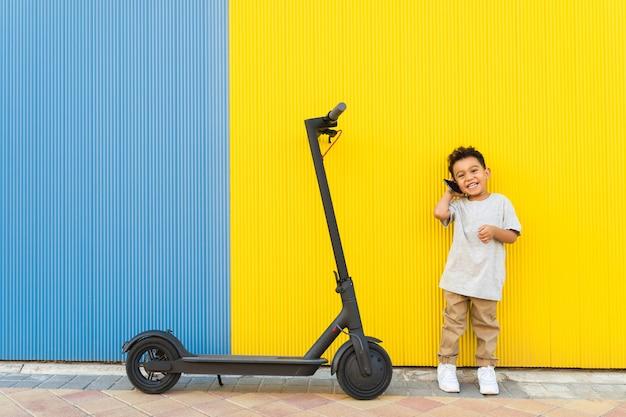 Klein kind met een telefoongesprek naast een scooter.