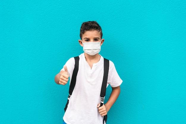 Klein kind met gezichtsmasker terug naar school met duimen omhoog