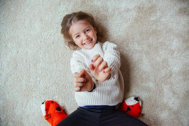 Klein kind met kietels op het tapijt