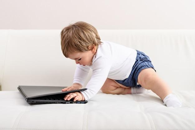 Klein kind met laptop op witte sofa, kinderbelang, kleine baas